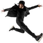Imaqen de clases de baile urbano de un chico vestido de negro sobre el escenario de las clases.