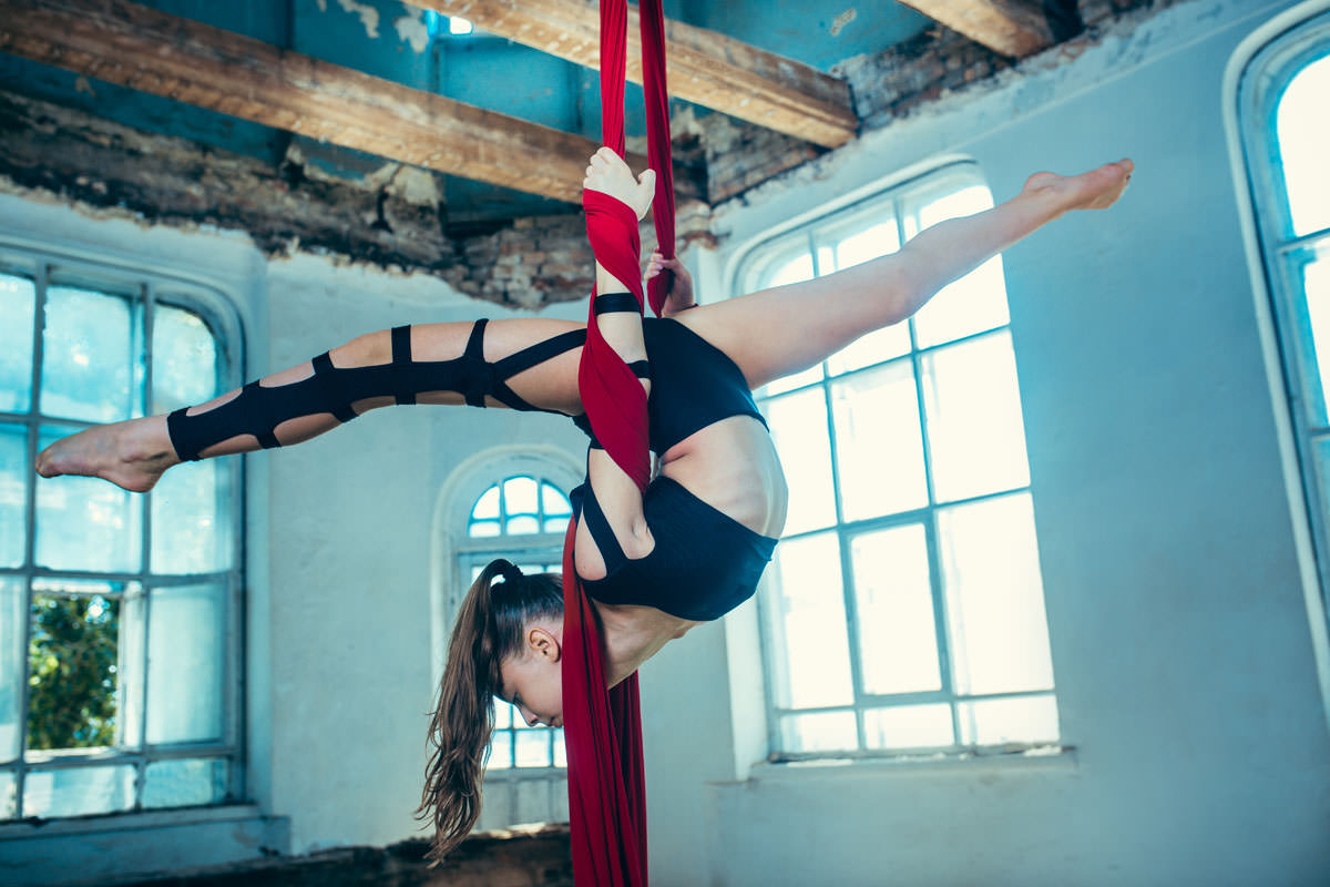 Graceful gymnast performing aerial exercise with red fabrics on blue old loft background. Young teen caucasian fit girl. The circus, acrobatic, acrobat, performer, sport, fitness, gymnastic concept