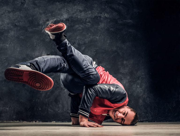 Bailarín de baile urbano realizando piruetas en el suelo