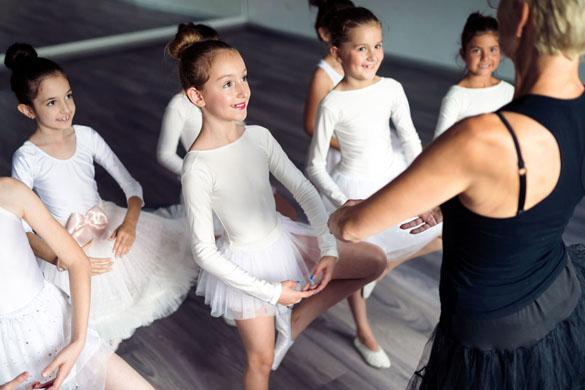 Niña en clases de ballet con zapatillas rosas.