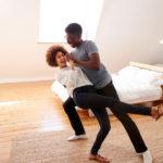 Pareja racial disfrutando de sus clases de baile online en el salón de su casa.