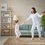 Madre e hija en clases de baile online, vestidas con pijama y saltando sobre la alfombra del salón de su casa en Toledo.